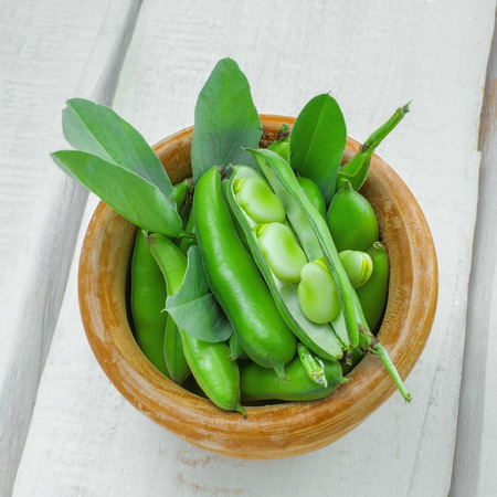 Fresh green broad beans in a bowl. Fresh raw vegetables on a wooden table. Ingredients healthy vegetarian food. Top view. Stock Photo