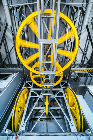steel cable: Rolling wheels of cable road mechanism with steel cable. Shot inside a control room. Stock Photo