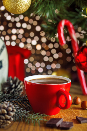 cup of hot cocoa beverage under christmas tree gift boxes on background traditional hot