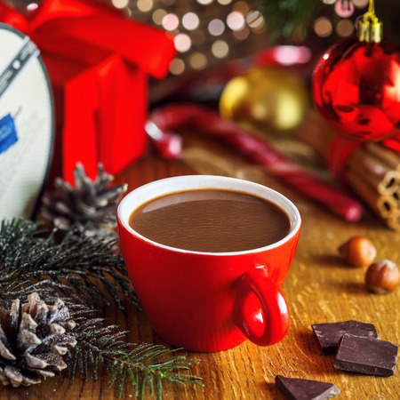 christmassy: Traditional Christmassy hot chocolate beverage and gift boxes under Christmas tree. Tasty cocoa drink. Stock Photo