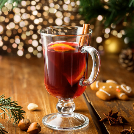 Mulled wine for Christmas Eve celebration party by Christmas tree. Hot traditional winter drink for New Year eve. Stock Photo