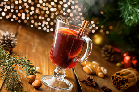 Glass of mulled wine on a table for a New Year party. Traditional alcohol hot drink by Christmas tree.