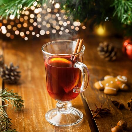 Mulled wine with citrus fruits and cinnamon on a table. Traditional winter hot drink for Christmas Eve party.  Stock Photo