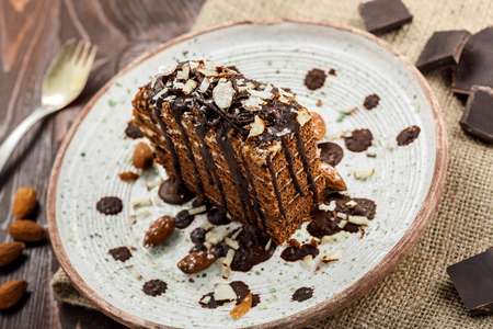 Piece of chocolate Spartak cake on a table. Delicious sweet food on a beautiful plate.