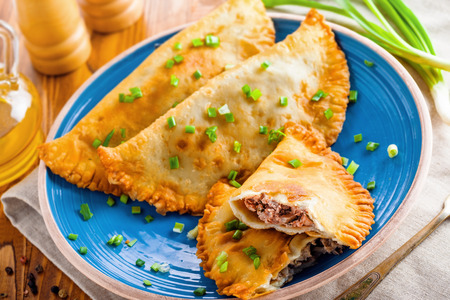 Russian, Turkish, Ukrainian and Tatar national meal cheburek. Traditional east cuisine food. Meat pastry on a table. Top view shot.