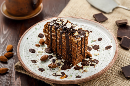 Slice of delicious chocolate Spartak cake on a rustic plate. First class dessert on a white wooden table.