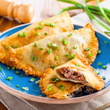 Chebureki with meat and spring onion. National Russian, Turkish, Ukrainian, Tatar and Romanian food on a table. Middle East traditional meat pastry.