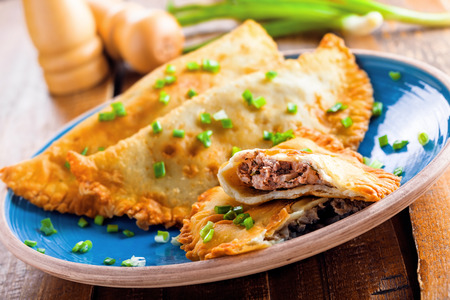 Traditional Romania, Ukrainian, Russian and Tatar food cheburek with meat and spring onion. National east meal. Meat pastry on a blue plate. Stock Photo
