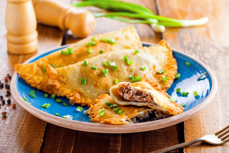 Native Russian, Turkish, Ukrainian, Romanian and Tatar food on a table. Delicious cheburek with meat and spring onion. East cuisine meat pastry. Stock Photo