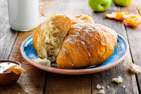 Two delicious croissants with jam, milk, fresh fruits and milk for healthy breakfast. Traditional French food on a rustic wooden table.