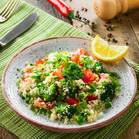 red quinoa: Vegetarian salad made of couscous, broccoli, tomato, pepper, onion and dill on a plate. Traditional Moroccan food for healthy meal on a table. Top view.