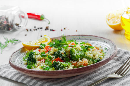 Plate with couscous and vegetables on a rustic wooden table. Traditional eastern healthy meal made of couscous, broccoli, tomato, pepper, onion and dill.