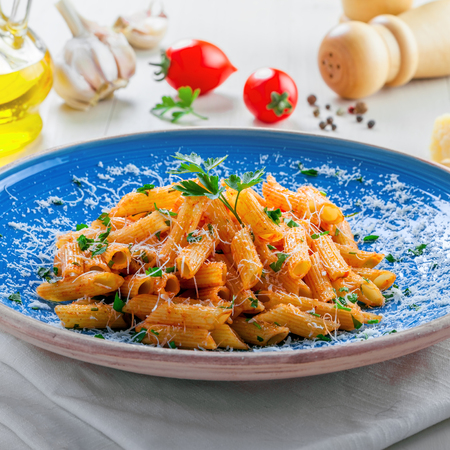 cooking oil: Traditional Italian meal made of penne pasta and arrabiata sauce with parsley on a white table. Delicious healthy Mediterranean food on a blue rustic plate.