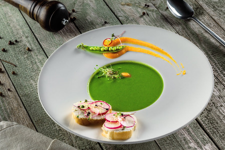 Delicious pea cream soup in a rim soup plate. Healthy traditional European cuisine food on a table. Stock Photo
