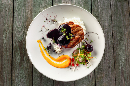 Delicious meat steak with rice, salad and sauce on a plate. Lunch healthy meal made of grilled meat and vegetable salad on a wooden table. Top view. Stock Photo