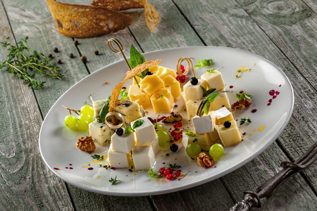 Gourmet cheese set of parmesan, gouda, gorgonzola, brie, camembert and other cheeses on plate. Cheese platter with fruits and appetizers on a wooden table.