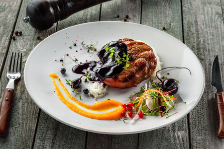 Gourmet meat steak, vegetable salad, sauce and rice on a plate. Delicious healthy meal made of grilled meat and vegetables on a rustic wooden table.