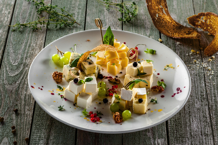 Cheese platter of parmesan, gouda, gorgonzola, brie, camembert and other cheeses with grape, basil and other appetizers on a wooden table.