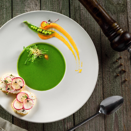 Pea cream soup in a rim soup plate. Classic European food on a rustic wooden table.