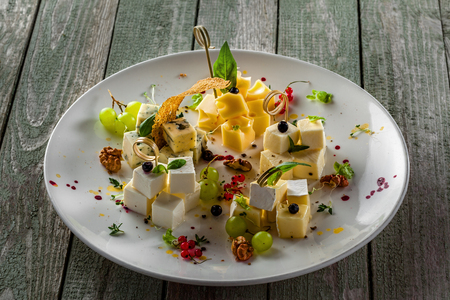Gourmet cheese set of parmesan, gouda, gorgonzola, brie, camembert and other cheeses on plate. Cheese platter with fruits and appetizers on a wooden table. Close-up.