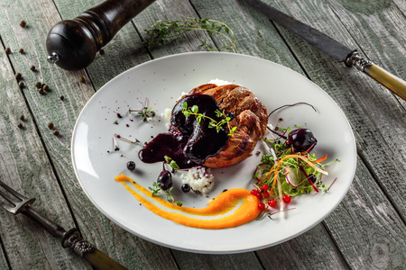 Plate with delicious steak, salad, sauce and rice on a wooden table. Healthy gourmet food made of meat and vegetables. Top view. Stock Photo