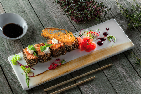 Traditional healthy Japanese meal sashimi made of salmon fish on a square plate. Fish rolls on a wooden table.