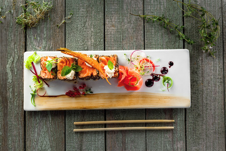 Delicious Japanese food sashimi. Salmon rolls on a square plate. Fresh healthy Asian seafood meal on a wooden table. Top view. Stock Photo