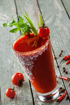 Glass of classic bloody mary cocktail on a rustic wooden table. Delicious alcoholic drink made of tomato juice, vodka, pepper, salt, lemon juice, celery and other flavorings. Close-up shot.