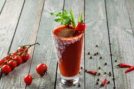 Bloody mary cocktail made of tomato juice, vodka, pepper, salt, lemon juice, celery and other flavorings. Classic alcoholic drink mix.