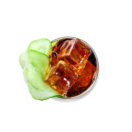Delicious alcoholic cocktail drink with cucumber, cola and brandy isolated on white background. Classic cocktail with ice. Top view close-up shot.