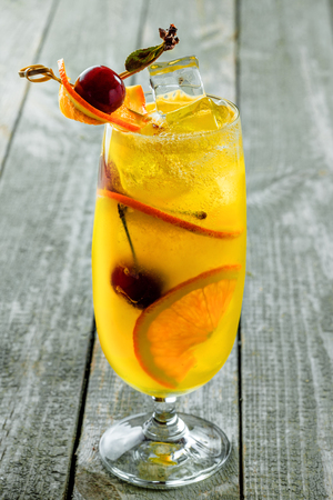 Alcoholic punch cocktail in a long glass. Delicious drink made of alcohol, fruit juice, orange and cherry on a table. Close-up vertical shot. Stock Photo