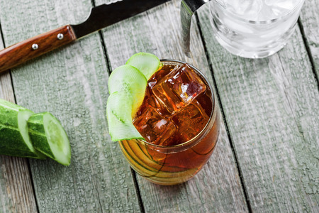 Glass of alcoholic cocktail Kreuzberger Schraube made of whiskey, cola, cucumber and ice. Alcoholic drink with ice on a rustic wooden table. Top view close-up shot.