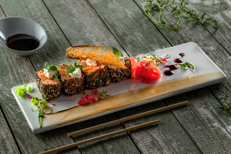 Delicious Japanese food sashimi. Salmon rolls on a square plate. Fresh healthy Asian seafood meal on a wooden table.