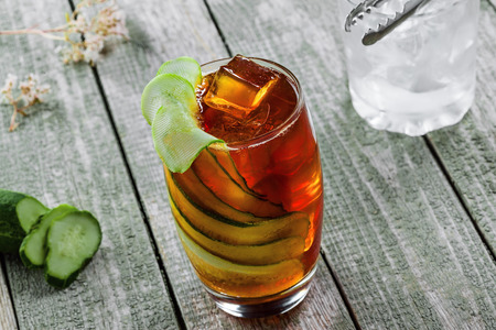 Alcoholic cocktail Kreuzberger Schraube in a glass made of cola, vodka, ale and cucumber. Delicious alcoholic beverage on a table. Stock Photo