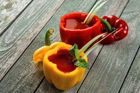 Classic bloody mary in in yellow and red sweet bell peppers a wooden table. Alcoholic drink made of tomato juice, vodka, pepper, salt, lemon juice, celery and other flavorings. Stock Photo