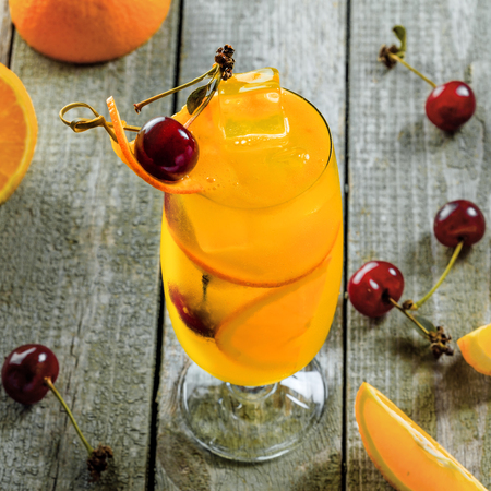 Fruit punch cocktail made of vodka, fruit juice, orange and cherry on a wooden table. Alcoholic drink in a long hurricane glass.