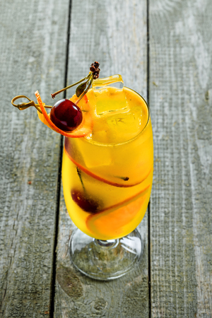 Alcoholic punch cocktail in a long glass. Delicious drink made of alcohol, fruit juice, orange and cherry on a table. Top view shot.