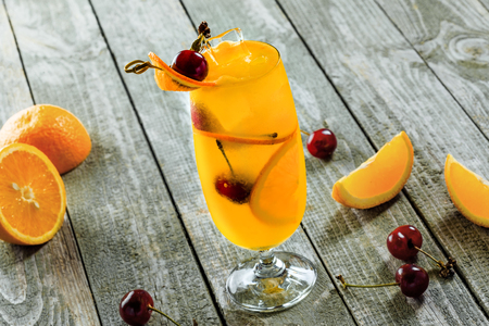 Delicious fruit punch cocktail made of fruit juice, orange, cherry and vodka on a wooden table. Alcoholic drink in a long hurricane glass. Stock Photo