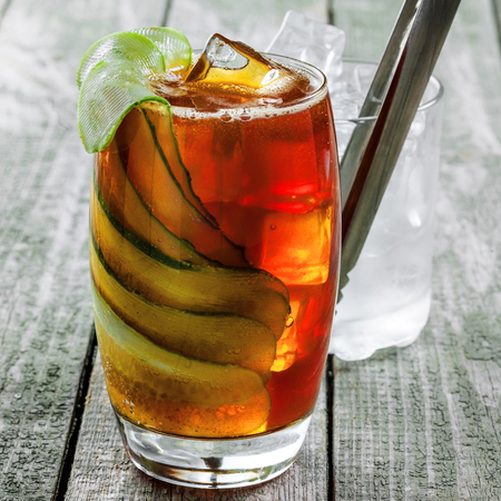 Delicious alcoholic cocktail drink with cucumber, cola and brandy on a wooden table. Classic cocktail with ice. Close-up shot.