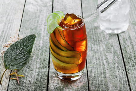 Glass of alcoholic cocktail Kreuzberger Schraube made of whiskey, cola, cucumber and ice. Alcoholic drink with ice on a rustic wooden table.