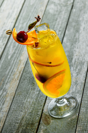 Alcoholic punch cocktail made of fruits and alcohol in a long glass on a wooden table.