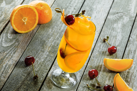 Alcoholic punch cocktail made of fruits and alcohol in a long glass on a wooden table. Close-up shot. Stock Photo