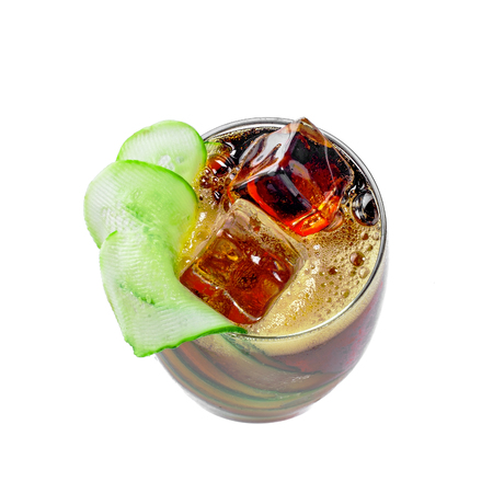 Alcoholic cocktail Kreuzberger Schraube in a glass made of cola, vodka, ale and cucumber. Delicious alcoholic beverage isolated on white background. Top view.