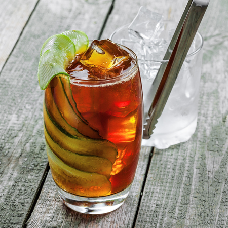 Classic alcoholic cold drink with ice, cucumber, cola and vodka in a glass. Cocktail with alcohol and cola on a wooden table.
