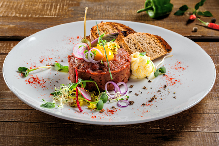 Tasty tartare with toasted bread and salad. Gourmet French meal made of raw ground meat. Delicious healthy food. Close-up shot.