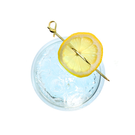 Glass gin and tonic cocktail with lemon slice isolated on a white background. Top view. Stock Photo