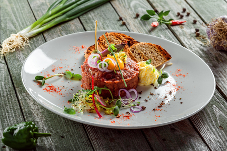 Delicious tartare with toasted bread and salad on a plate. Healthy lunch meal made of raw meat. Classical French cuisine. Stock Photo
