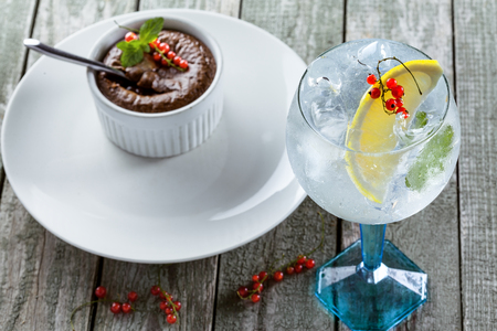 Glass of gin and tonic cocktail with sweet chocolate mousse on a wooden table. Stock Photo