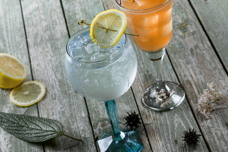 Gin and tonic cocktail with drink made of rum, soda, ice and basil leaf on a wooden table. Alcoholic drinks in a glass. Stock Photo