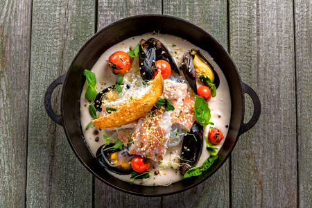 Bowl of delicious seafood meal with rice noodles. Meal made of sea bass fish, mussels, crab meat and other seafood with vegetables on a table. Top view.
